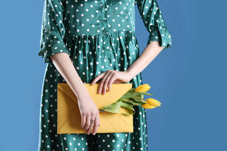 Woman holding elegant clutch with spring flowers on blue background, closeup. Space for text