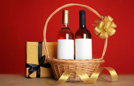 Bottles of wine in wicker basket with bow and gift on table against color background 写真素材