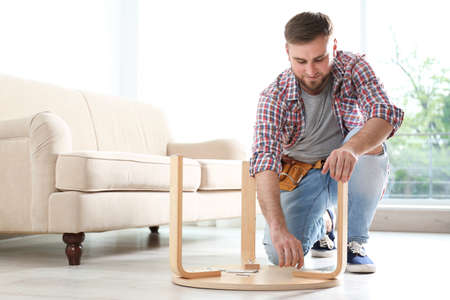 Young man working with wooden chair indoors. Space for text
