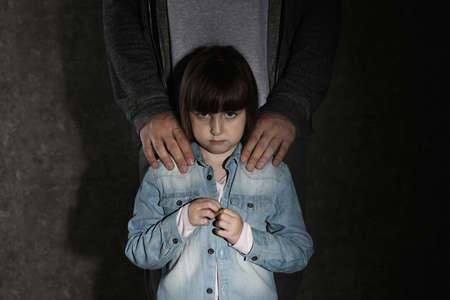 Erschrockenes kleines Mädchen und erwachsener Mann auf dunklem Hintergrund. Kind in Gefahr Standard-Bild