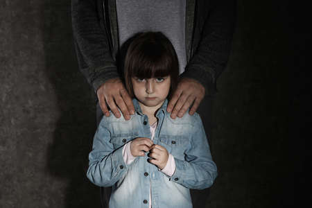 Scared little girl and adult man on dark background. Child in danger