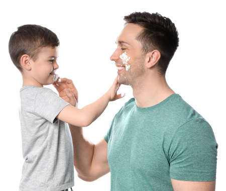 Dad and his little son applying shaving foam against white background