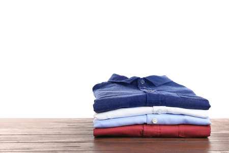 Pile of ironed clothes on table against white background. Space for text