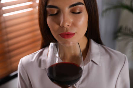 Beautiful young woman with glass of luxury red wine indoors, closeup view