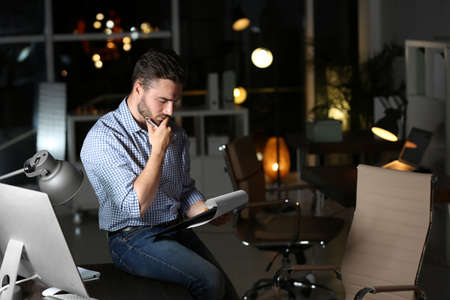 Young man working in office at night. Space for text