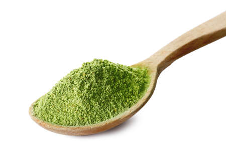 Wheat grass powder in wooden spoon on white background