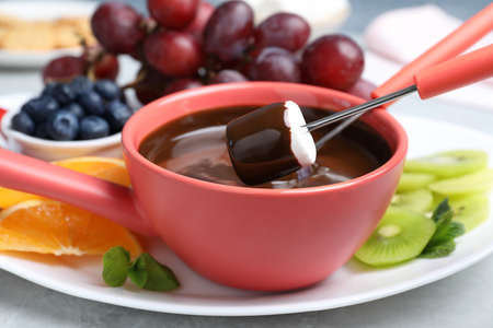 Dipping marshmallow into pot with chocolate fondue on table, closeup Archivio Fotografico
