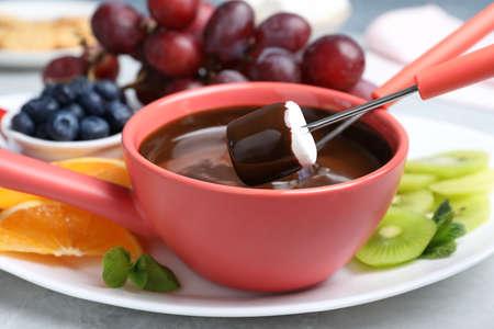 Dipping marshmallow into pot with chocolate fondue on table, closeup Stock fotó