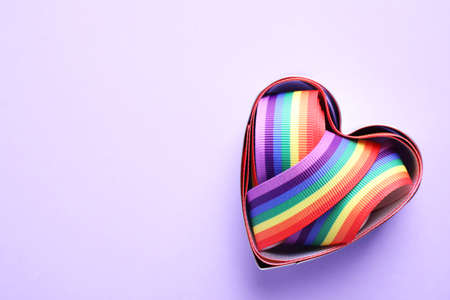 Heart shaped mold and bright rainbow ribbon on color background, top view with space for text. Symbol of gay community
