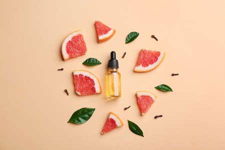 Composición laicos plana con rodajas de pomelo y una botella de aceite esencial sobre fondo de color