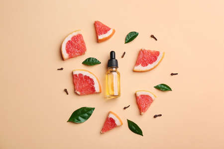 Flat lay composition with grapefruit slices and bottle of essential oil on color background Imagens