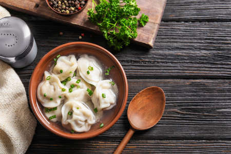 Bowl of tasty dumplings served on wooden table, flat lay. Space for text