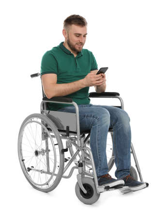 Young man in wheelchair with mobile phone isolated on white