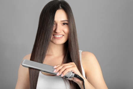 Young woman using hair iron on grey background, space for text
