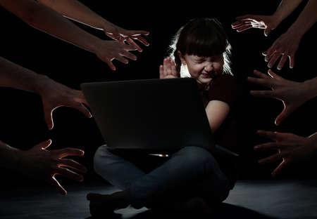 Strangers reaching frightened little child with laptop on dark background. Cyber danger