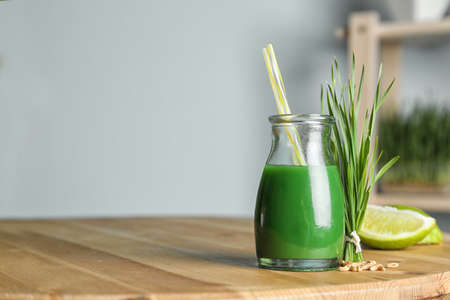 Bottle of juice and fresh wheat grass on table. Space for text