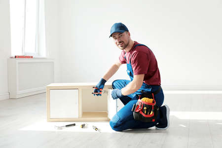 Handyman in uniform assembling furniture indoors. Professional construction tools