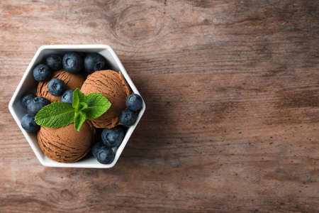 Bowl of chocolate ice cream and blueberries on wooden table, top view. Space for text