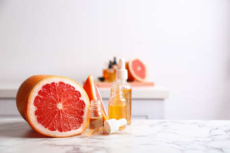 Bottles of essential oil and grapefruit slices on table. Space for text Stock Photo