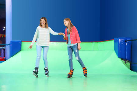 Woman and her daughter having fun at roller skating rink