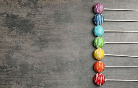 Bright delicious cake pops on dark background, flat lay. Space for text