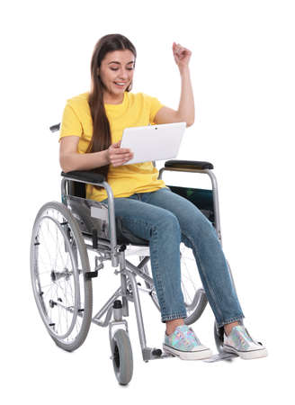 Happy young woman in wheelchair with tablet isolated on white