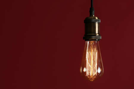 Pendant lamp with light bulb against dark red background, space for text