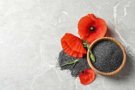 Cuenco de madera de semillas de amapola y flor en mesa gris, plano con espacio para texto Foto de archivo