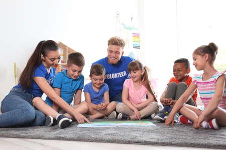 Young volunteers reading book with children on floor indoors