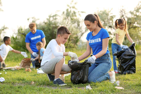 Little boy collecting trash with volunteer in park Banque d'images