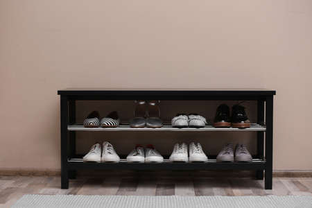Shoe rack with different footwear near color wall. Stylish hallway interior