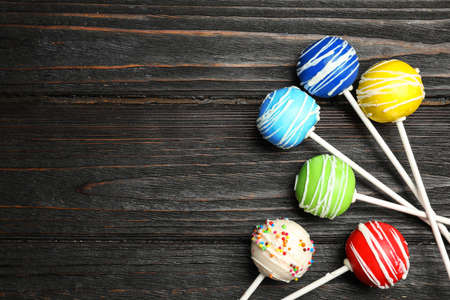 Bright delicious cake pops on wooden table, flat lay. Space for text
