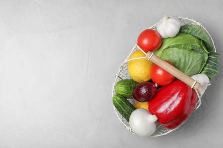 Basket with ripe fruits and vegetables on light table, top view. Space for text 스톡 콘텐츠