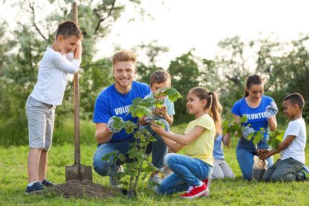 Niños plantando árboles con voluntarios en el parque. Foto de archivo