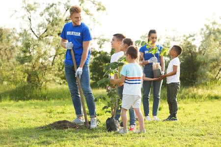 Kids planting trees with volunteers in park 版權商用圖片