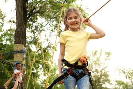 Little girl climbing in adventure park. Summer camp