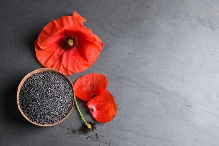 Cuenco de madera de semillas de amapola y flor en mesa gris, plano con espacio para texto