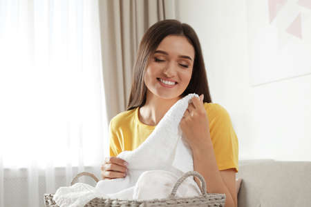 Young woman with laundry basket full of clean towels indoors