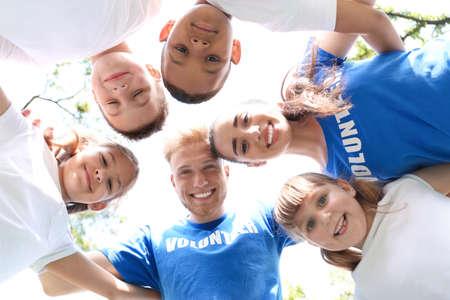 Niedrigwinkelansicht von Freiwilligen, die sich mit Kindern im Park zusammendrängen