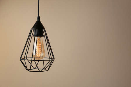 Hanging lamp bulb in chandelier against beige background, space for text