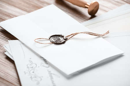 Document with notary seal and papers on wooden table, closeup