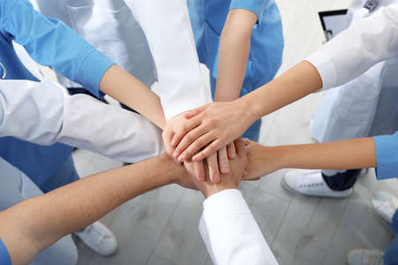 Team of medical workers holding hands together indoors, above view. Unity concept Stock fotó