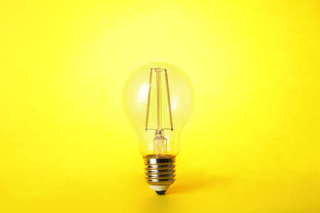 Vintage filament lamp bulb on yellow background