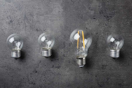 Vintage and modern lamp bulbs on grey stone surface, top view