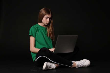 Shocked teenage girl with laptop on black background. Danger of internet