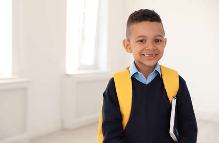 Portrait of cute African-American boy in school uniform with backpack and book indoors. Space for text