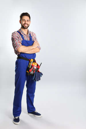 Full length portrait of construction worker with tool belt on light background. Space for text