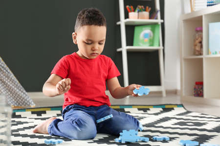 Cute little African-American child playing with puzzles on floor in kindergarten. Indoor activity Stock Photo