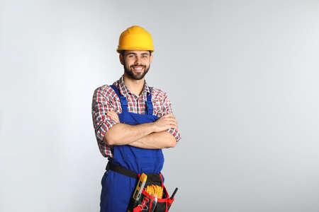 Porträt des Bauarbeiters mit Werkzeuggürtel auf hellem Hintergrund. Platz für Text