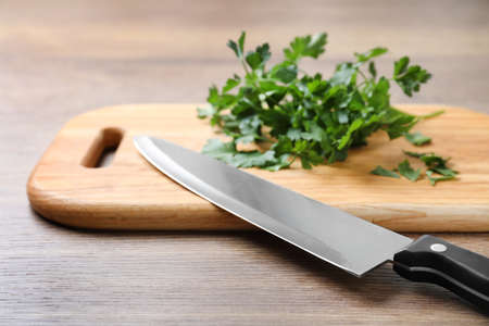 Cutting board with chef's knife and fresh parsley on wooden table